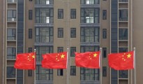 Chinese national flags fly in front of a newly-built residential apartment in Wuhan, Hubei province July 10, 2012. China must firmly maintain its property tightening measures to cool housing prices, Premier Wen Jiabao was quoted as saying, underscoring official concerns about renewed bubbles as the central bank ratchets up policy easing to support growth.