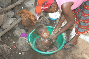 A mother tries to keep her baby clean in Kroo Bay