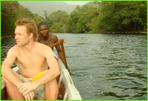 Tribewanted Sierra Leone co-founder Ben Keene canoeing in the river near John Obey