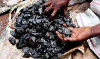 A Congolese miner checks his load of mineral chips he got inside a deep cassiterite mine in the north Kivu region