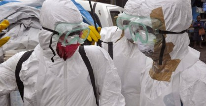 Health workers in protective gear leave after carrying the body of a woman that they suspect died from the Ebola virus, in an area known as Clara Town in Monrovia, Liberia, Wednesday, Sept. 10, 2014. A surge in Ebola infections in Liberia is driving a spiraling outbreak in West Africa that is increasingly putting health workers at risk as they struggle to treat an overwhelming number of patients. A higher proportion of health workers has been infected in this outbreak than in any previous one.