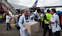 Cuban health workers unload medical supplies at Freetown's airport to help fight Ebola in Sierra Leone. Charities say the UK flight decision closes a vital humanitarian corridor to the country.