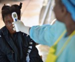 girls suspected of being infected with the Ebola virus has her temperature checked at the government hospital in Kenema, Sierra Leone, on August 16, 2014