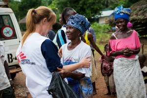 Medical staff chat with Abnach Bayu, a recovered Ebola victim, in her village Pendembu.
