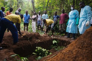 Red Cross workers bury the body of a suspected Ebola victim in a remote area in the bush.