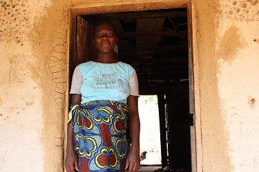Adama stands at the front door of her home in Maforay village. Continuing her education is allowing her to get closer to her dream of becoming a nurse.